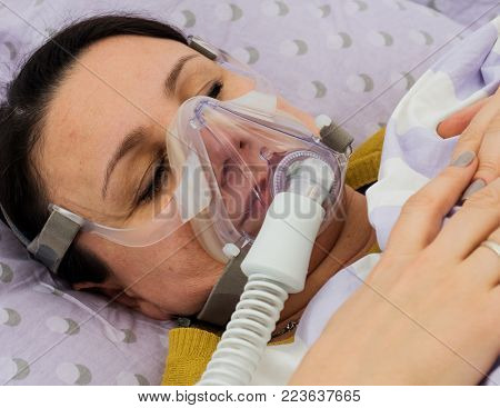 An adult woman in an oxygen mask in a hospital