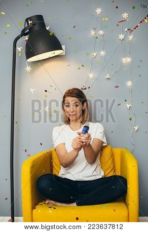 Young woman in white t-shirt blast confetti on yellow chair with grey wall and black floor lamp on background