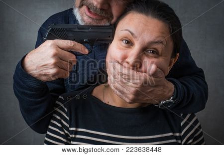 Killer and his victim. A man with a gun at woman's temple