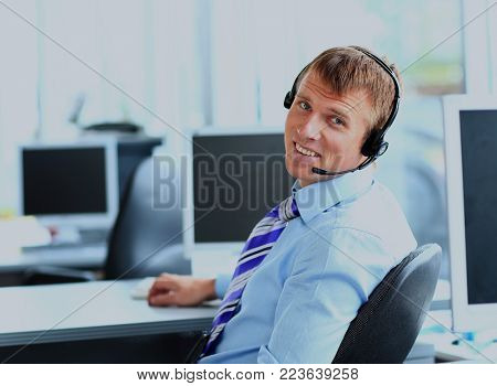 Happy young man working at callcenter, using headset.