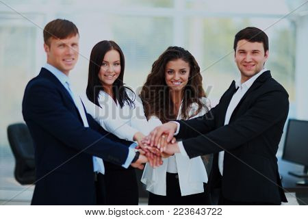 Group of business people piling up their hands together.