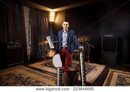 professional musician with studio keyboard synthesizer, accordion and harmonic