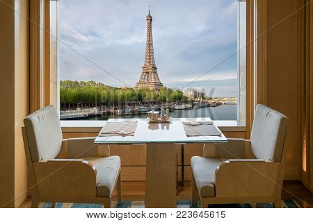 Modern luxury restaurant interior with romantic sence Eiffel Tower and Seine river view in Paris, France. Dinning table in restaurant at Paris, France.
