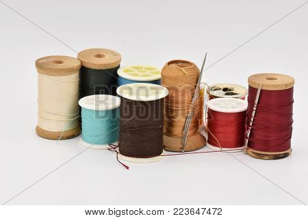 Assorted spools of thread in various colors, including blue, red, orange, black, and gold, on a seamless white background.