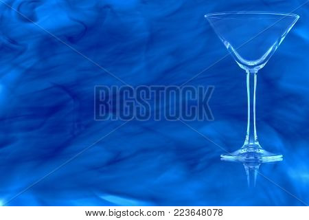 Empty the Martini glass on white background enveloped in puff of blue smoke.
