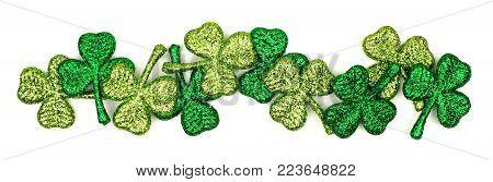 Border of St Patricks Day shiny shamrocks over a white background
