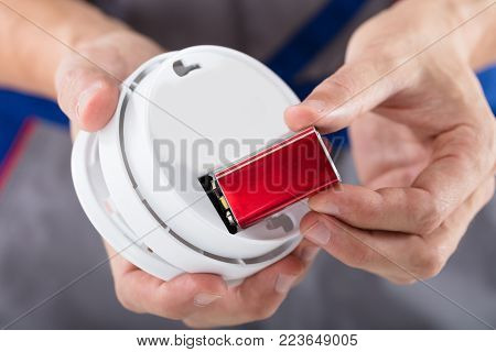 Close-up Of A Person's Hand Inserting Battery In Smoke Detector poster