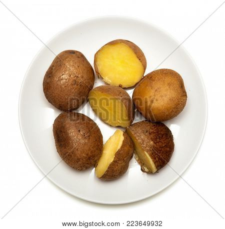 unpeeled boiled potatoes on a white plate, isolated on white background