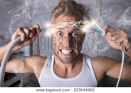 Portrait Of A Man Holding Bared Wires And Screaming Of Pain