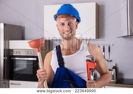 Portrait Of A Smiling Young Plumber Holding Wrench And Plunger In Kitchen At Home