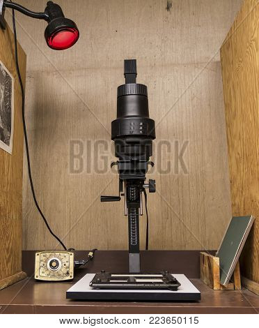 A enlarger in a darkroom set up to print black and white photos.