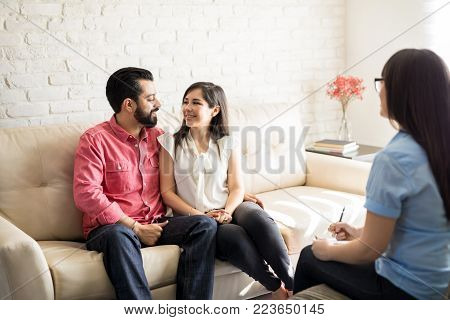 Counselor and happy young hispanic couple after effective marital therapy