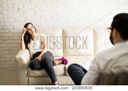 Pretty young hispanic female patient sitting on couch and sharing problems with male psychotherapist