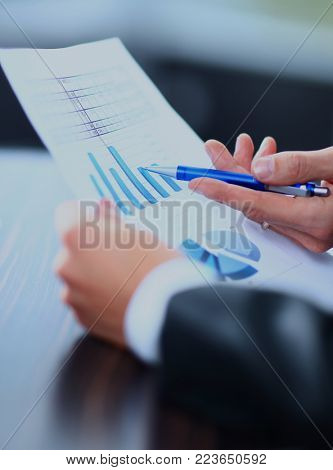Image of male hand pointing at business document during discussion at meeting.