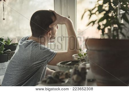 Young handsome man sitting at his home, feeling lonely and depressed, beating himself up