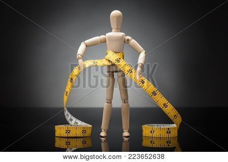 Wooden Dummy Measuring Waist With Yellow Measure Tape On Grey Background