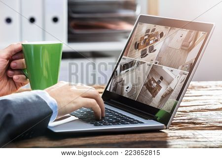 Close-up Of A Businessperson's Hand Monitoring Video Footage On Laptop Over Wooden Desk