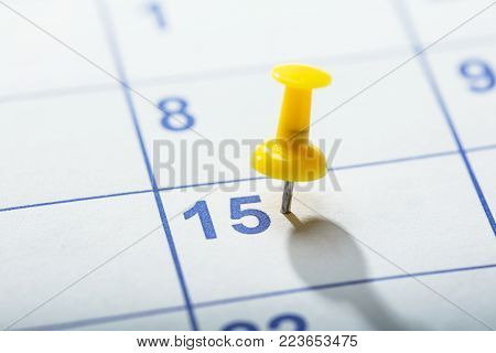 Close-up Of Yellow Thumbtack Stuck On Date 15th In Calendar