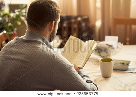 Young man enjoying a great piece of writing, a new bestseller, enjoying his hobby