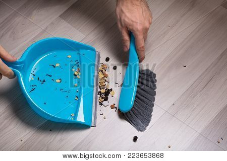 Close-up Of Male Sweeping Wooden Floor With Small Whisk Broom And Dustpan