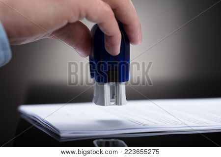 Close-up Of A Businessperson's Hand Stamping On Approved Contract Form