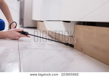 Close-up Of A Pest Control Worker's Hand Spraying Pesticide On Wooden Cabinet