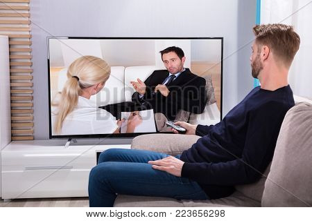 Side View Of A Young Man Sitting On Sofa Watching Television