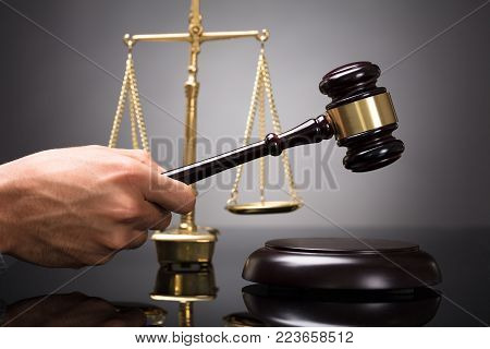 Judge Striking Gavel On Sounding Block In Front Of Golden Weighing Scale