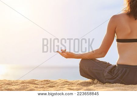 Woman Playing Yoga And Exercise On The Tropical Beach In Sunset Time. View From Back Side. With Spac
