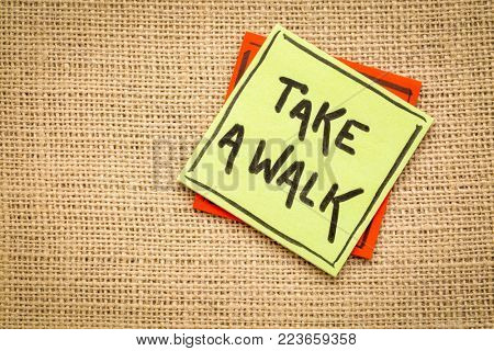 take a walk reminder - handwriting on a sticky note against burlap canvas