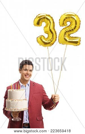 Elegantly dressed man holding a birthday cake and a number thirty-two shaped balloon isolated on white background