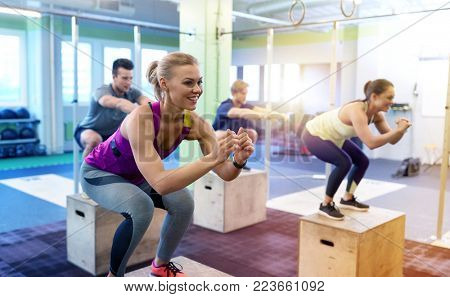 fitness, sport, training and exercising concept - group of people with heart-rate trackers doing box jumps in gym poster