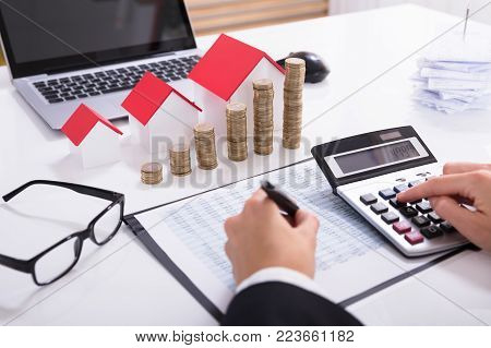 Businessperson Calculating Tax In Front Of House Models And Stacked Coins With Eyeglasses And Calculator
