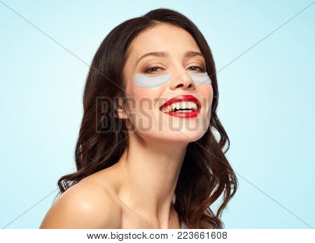 beauty, skin hydration and people concept - happy smiling young woman with hydrogel eye patches over blue background