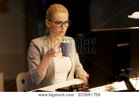 business, deadline and technology concept - businesswoman with computer working at night office and drinking coffee