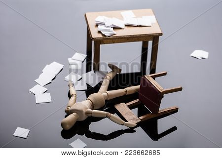 Unconscious Wooden Dummy Figure Lying On Floor With Scattered Documents At Workplace