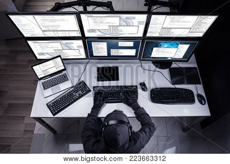 High Angle View Of A Hacker Stealing Information From Multiple Computers In Office