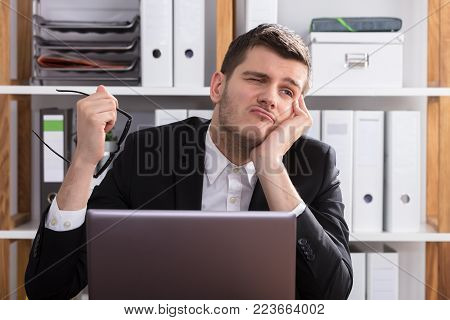 Contemplated Young Businessman Sitting Behind Laptop In Office