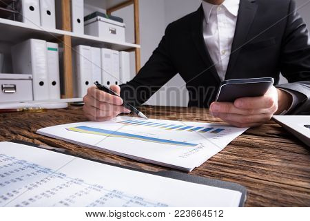 Businessperson's Hand Checking Financial Graph On Wooden Desk