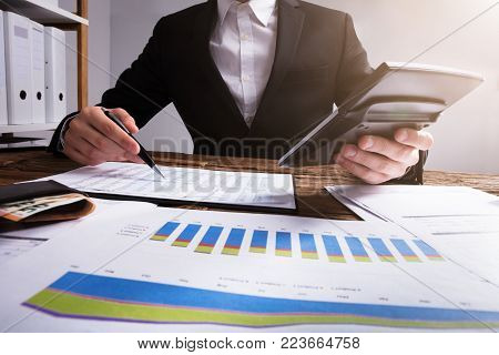 Businessperson Calculating Financial Report With Graphs And Wallet Wooden Desk