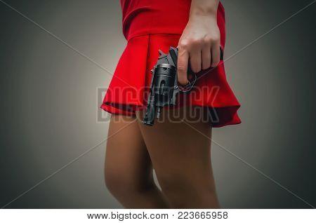 Girl in a red dress hides her pistol gun behind her back. Hidden threat. Killer woman.