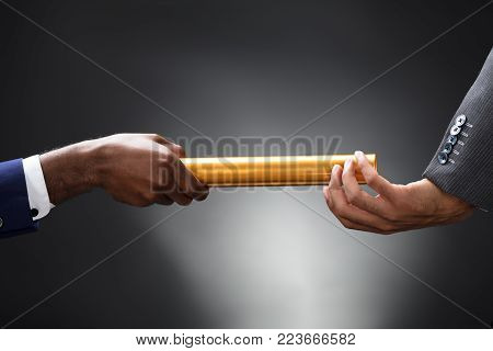 Man Passing The Golden Baton To His Partner On Gray Background