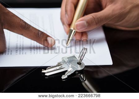 Close-up Of A Person's Hand Signing Contract With Keys On It