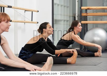Pretty young women doing stretching exercise in ballet class
