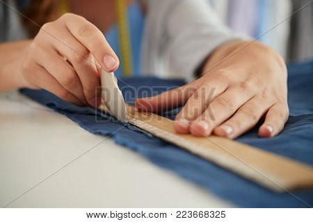 Close-up image of tailor drawing stright line on fabric with white chalk