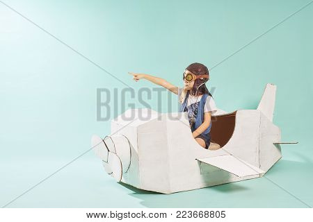 Little cute girl playing with a cardboard airplane. White retro style cardboard airplane on mint green background . Childhood dream imagination concept .