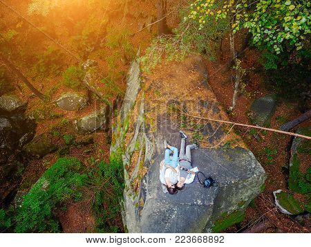 Top down aerial drone image of a forest, couple lies on a rock