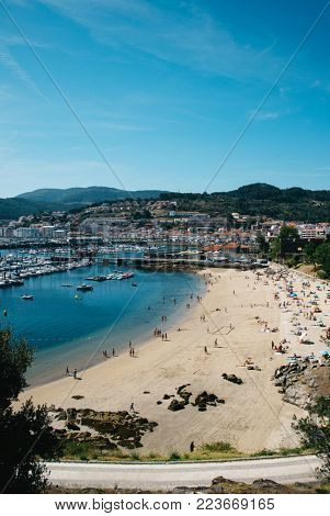 Beautiful beach on the coast of the Atlantic Ocean with yachts in dock summer sunny day, Bayona, Northen Spain