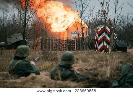 German soldiers Wehrmacht in a trench in the background of a burning building in the village
