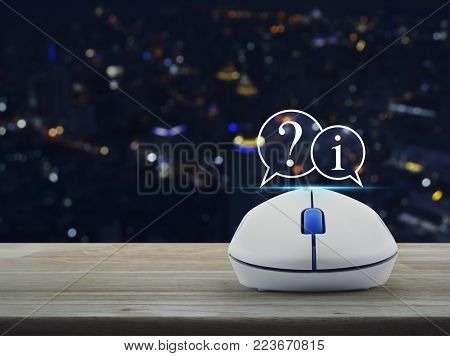Question mark and information chat icon with wireless computer mouse on wooden table over blur colorful night light city tower, Customer support concept